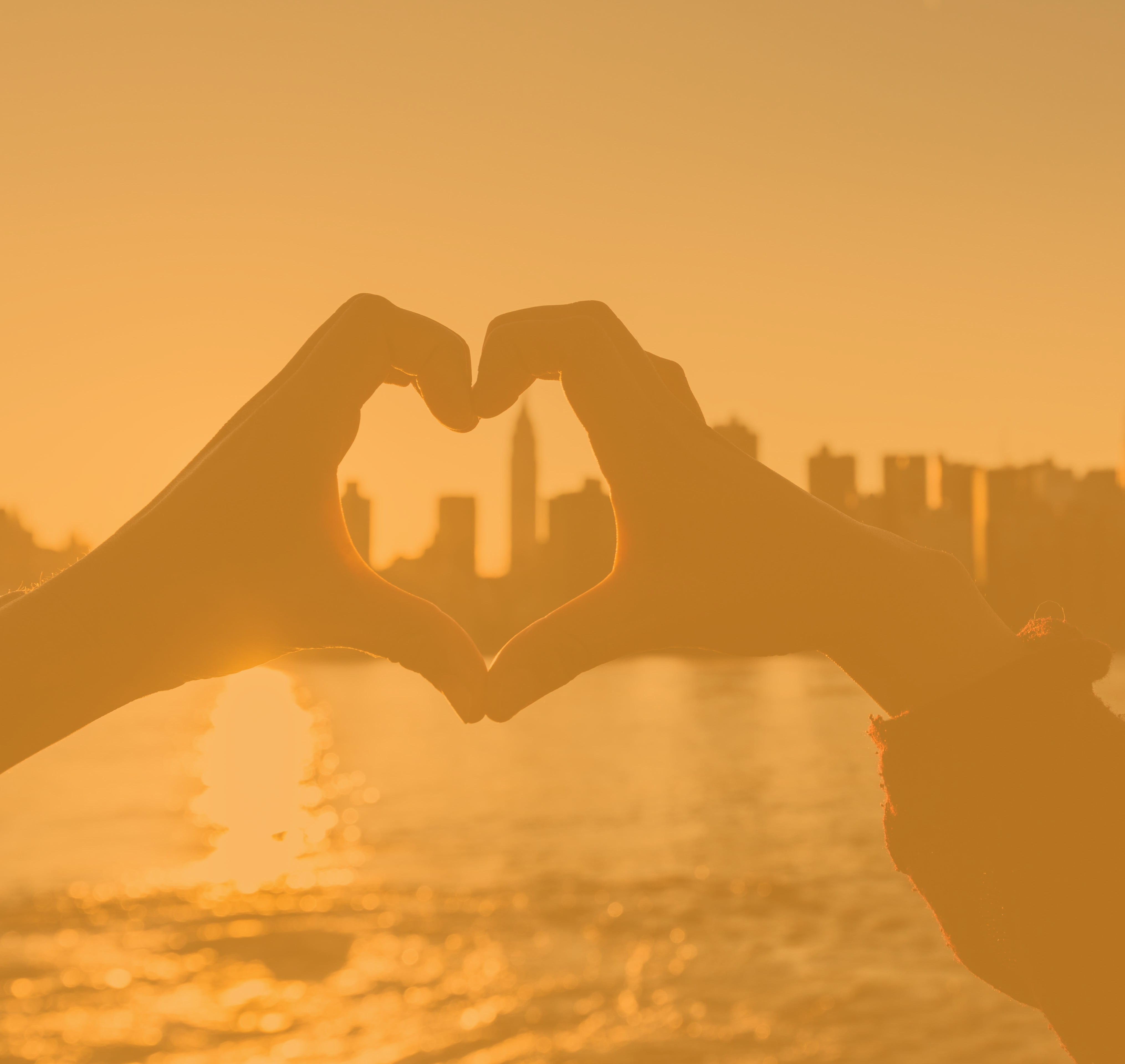 Hands forming a heart around a skyline