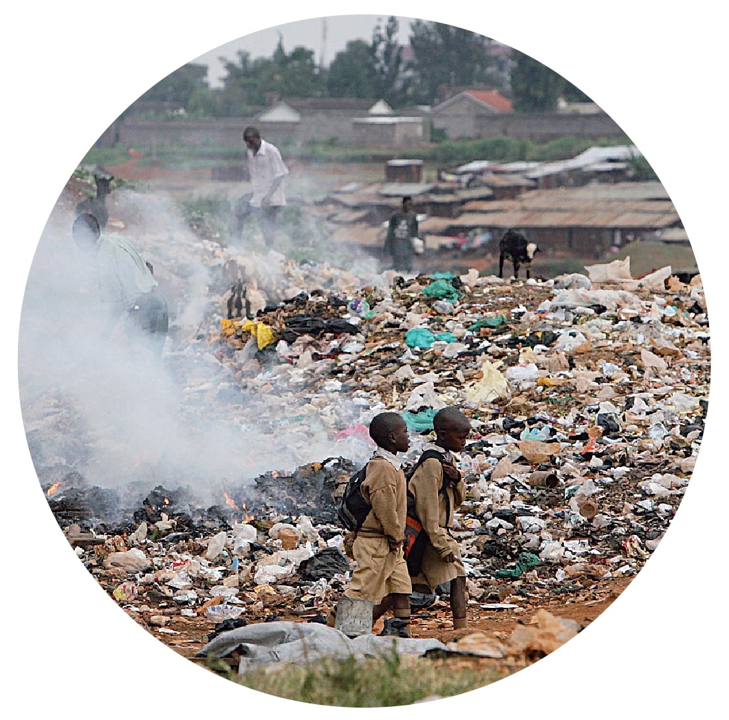 Two children walking in front of a mountain of trash and smoke.