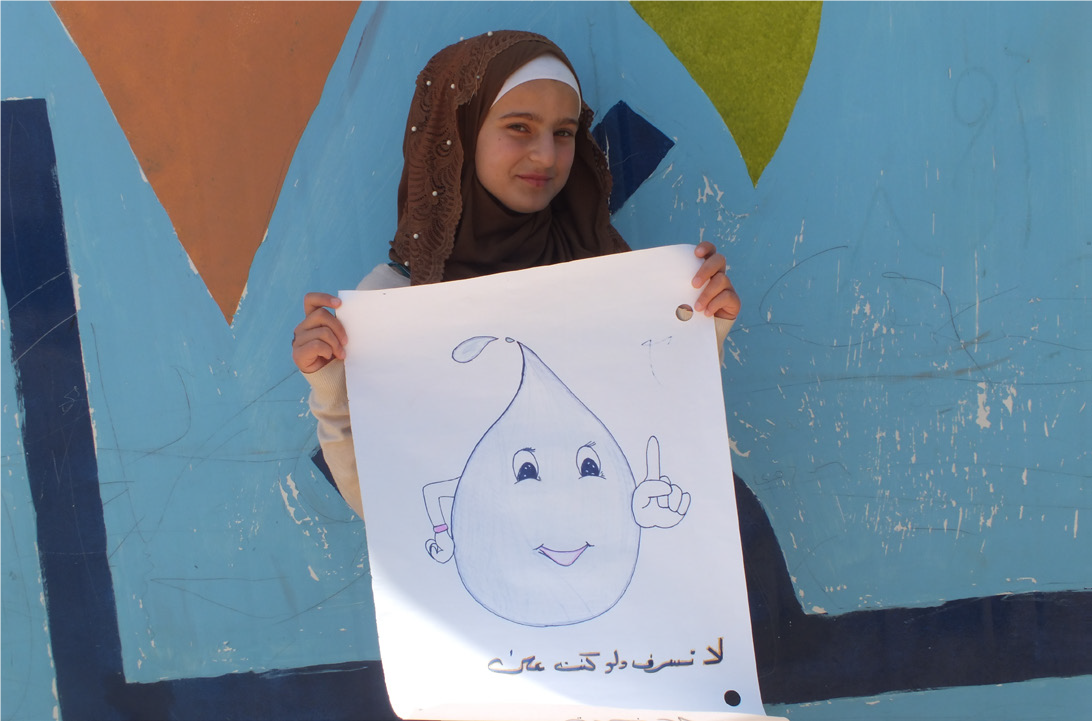 Wardeh in front of one of the Makani Centre caravans with her drawing on water conservation