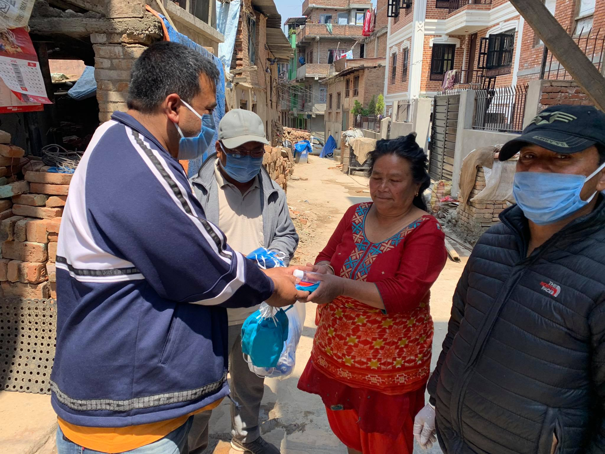 Local officials in Nepal hand out masks to protect against COVID-19 made by local handicraft workers ©UN-Habitat