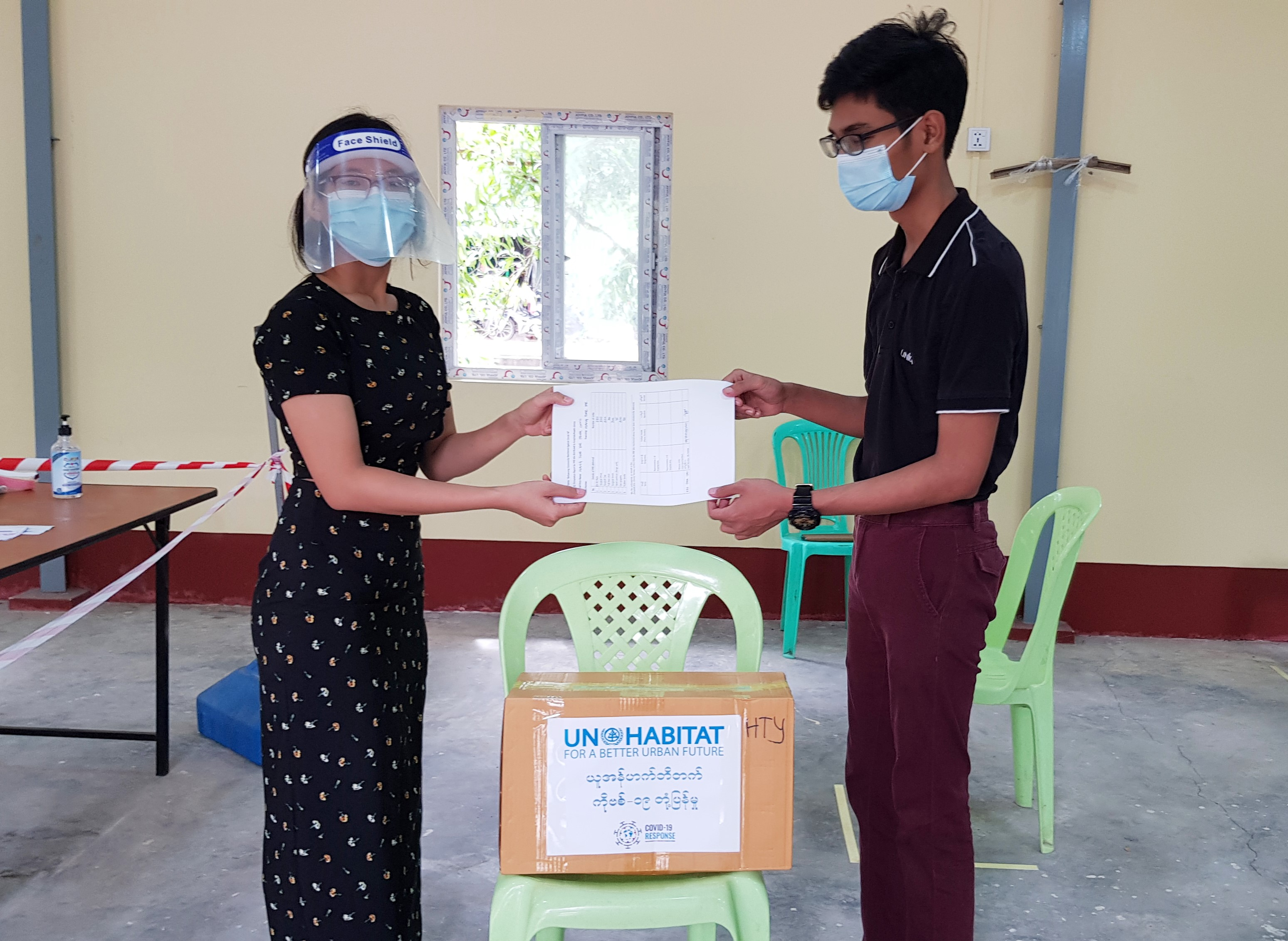 A UN-Habitat Staff member hands over the protective equipment to a representative from the Hlaingthayar fever clinic in Yangon, Myanmar to protect against COVID-19