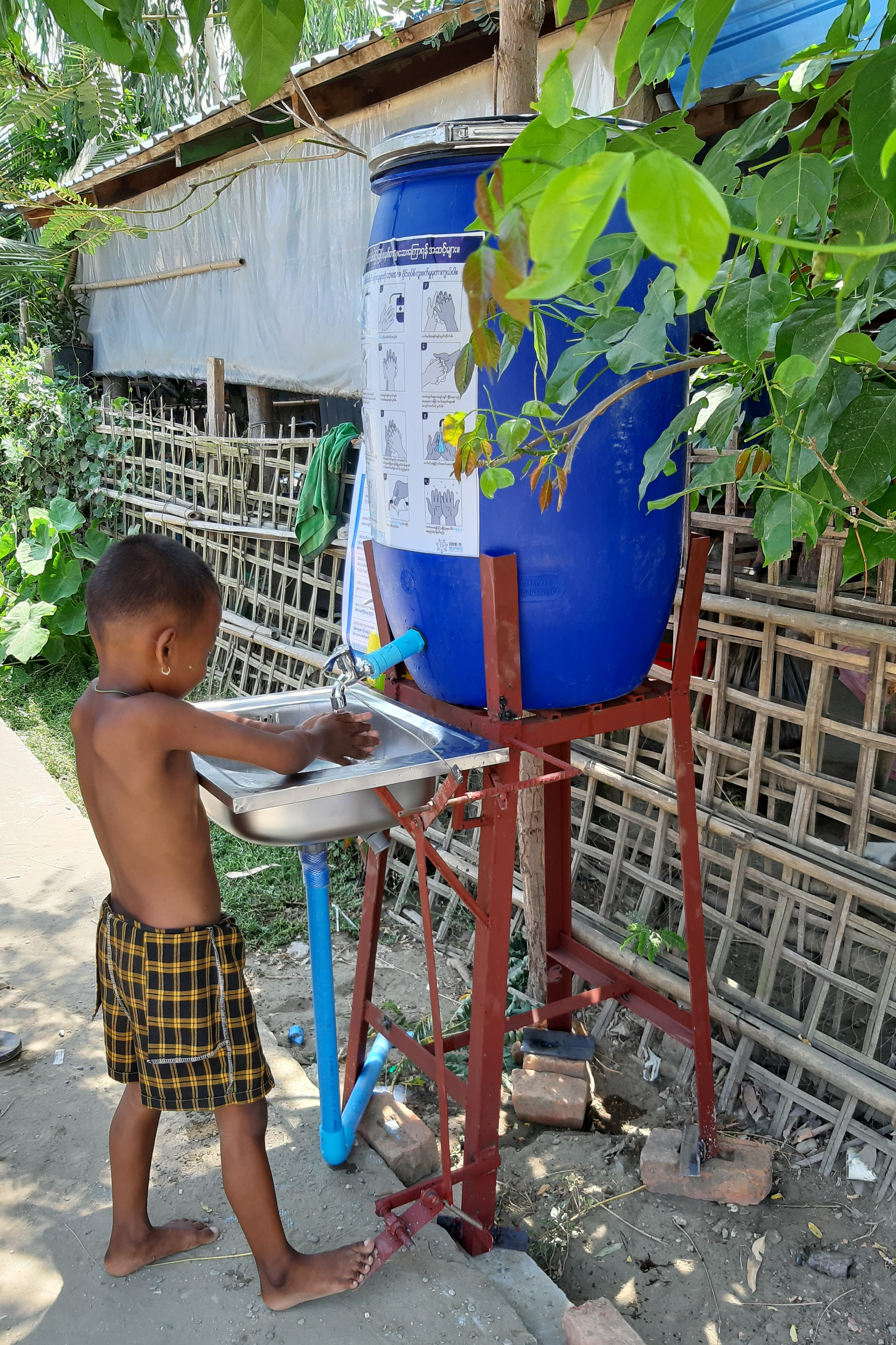 A child learns how to use the hands-free, foot pedal operated handwashing stations provided by UN-Habitat for COVID-19 prevention in Sittwe, Myanmar ©UN-Habitat /San Shwe Kyaw