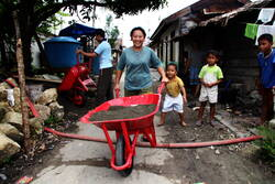 Woman pushing a wheelbarrow