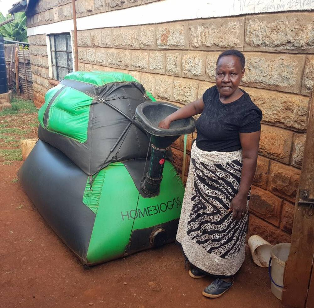 A woman uses a Homebiogas unit in her backyard