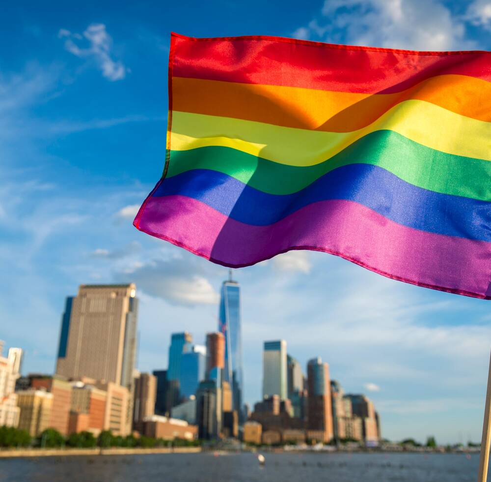 Rainbow-coloured flag in front of a city.
