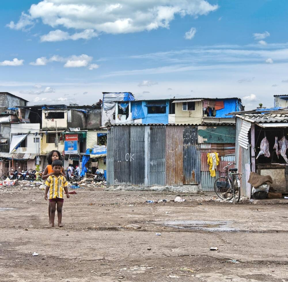 Two children standing in front of slum houses.
