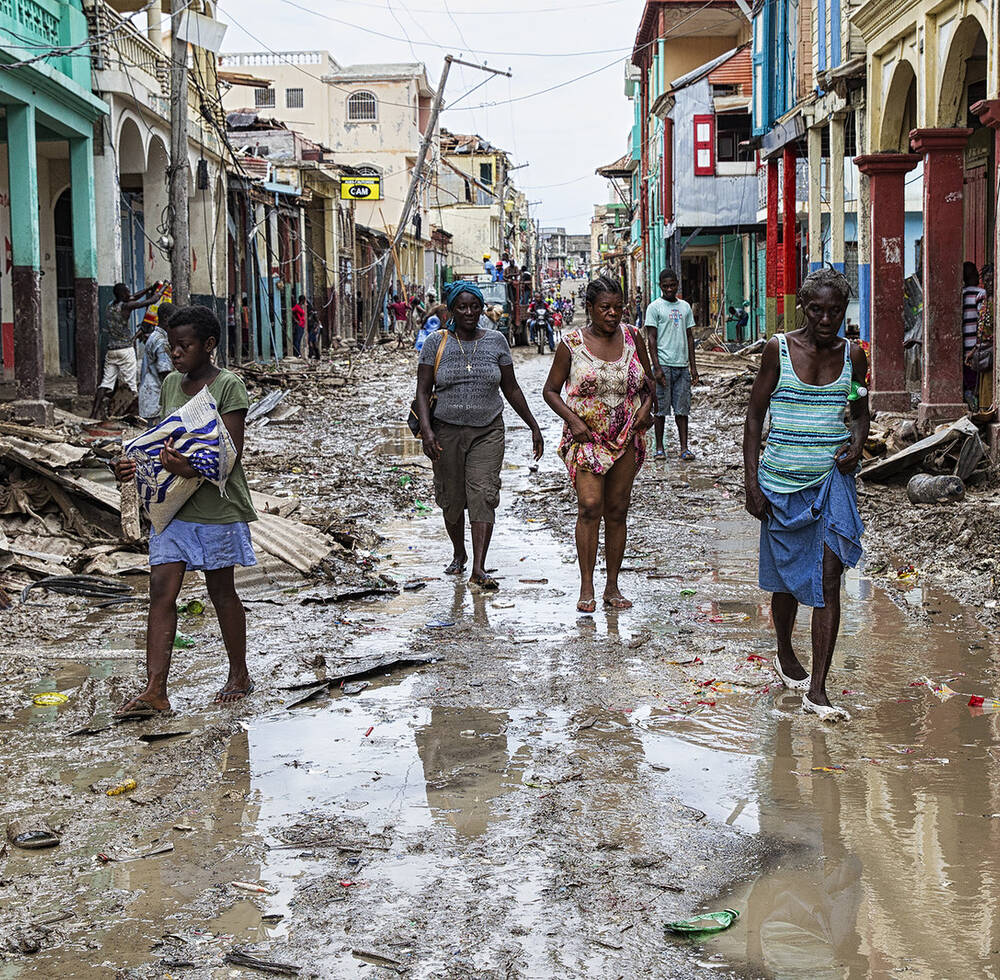 People walk along a street in downtown Jeremie Haiti in 2016 after Hurricane Matthew