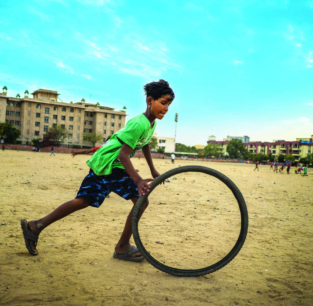 A girl play with a bycicle wheel