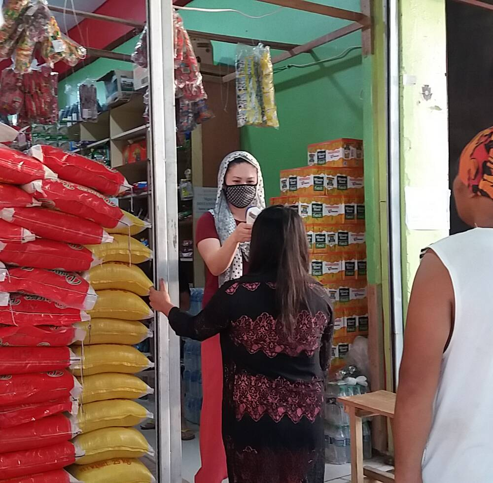 Customers have their temperatures taken before entering a shop in Marawi City, the Philipppines