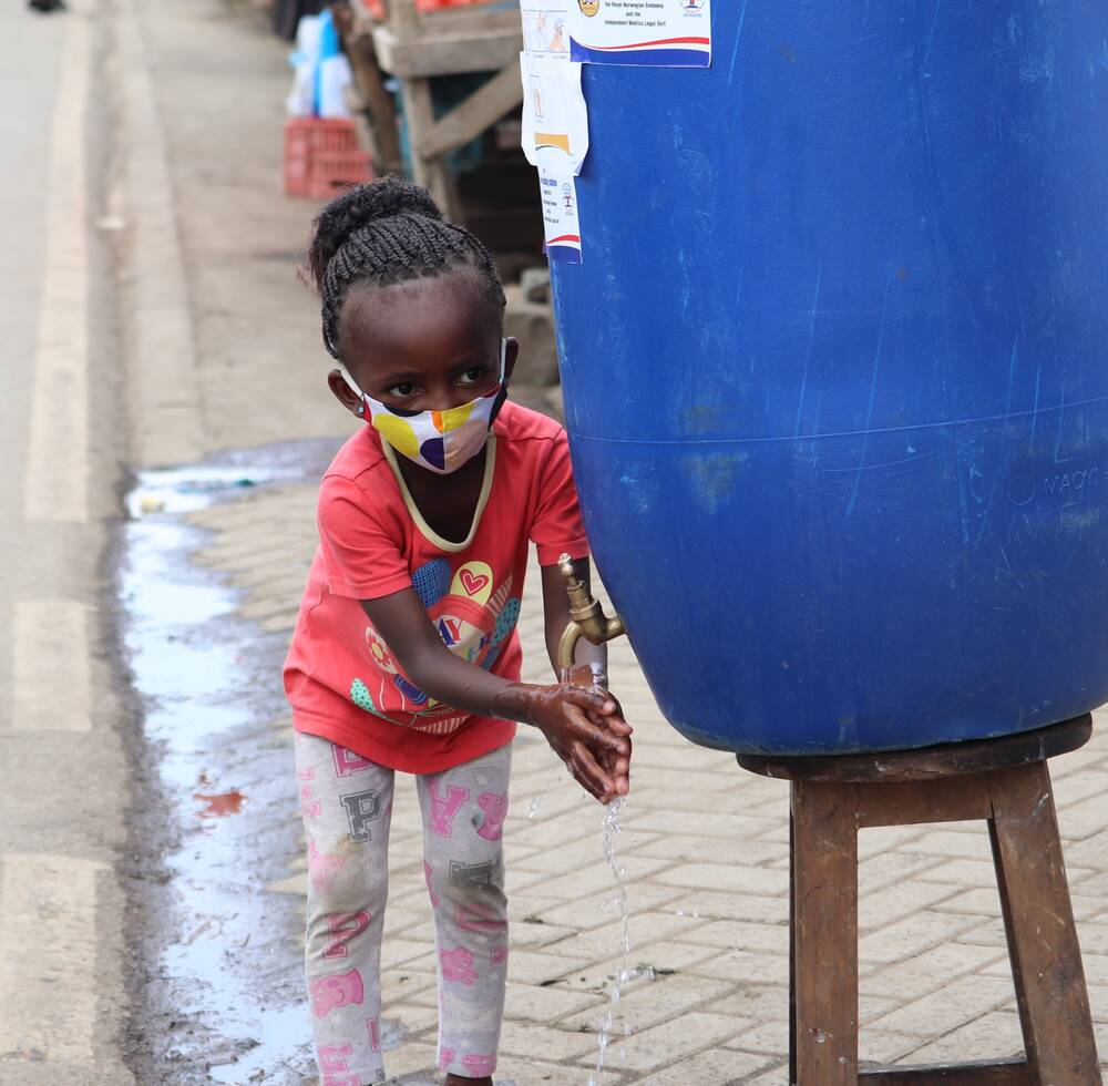 A child washes her hands at the UN-Habitat handwashing unit at Mathare informal settlement in the Kenyan capital, Nairobi
