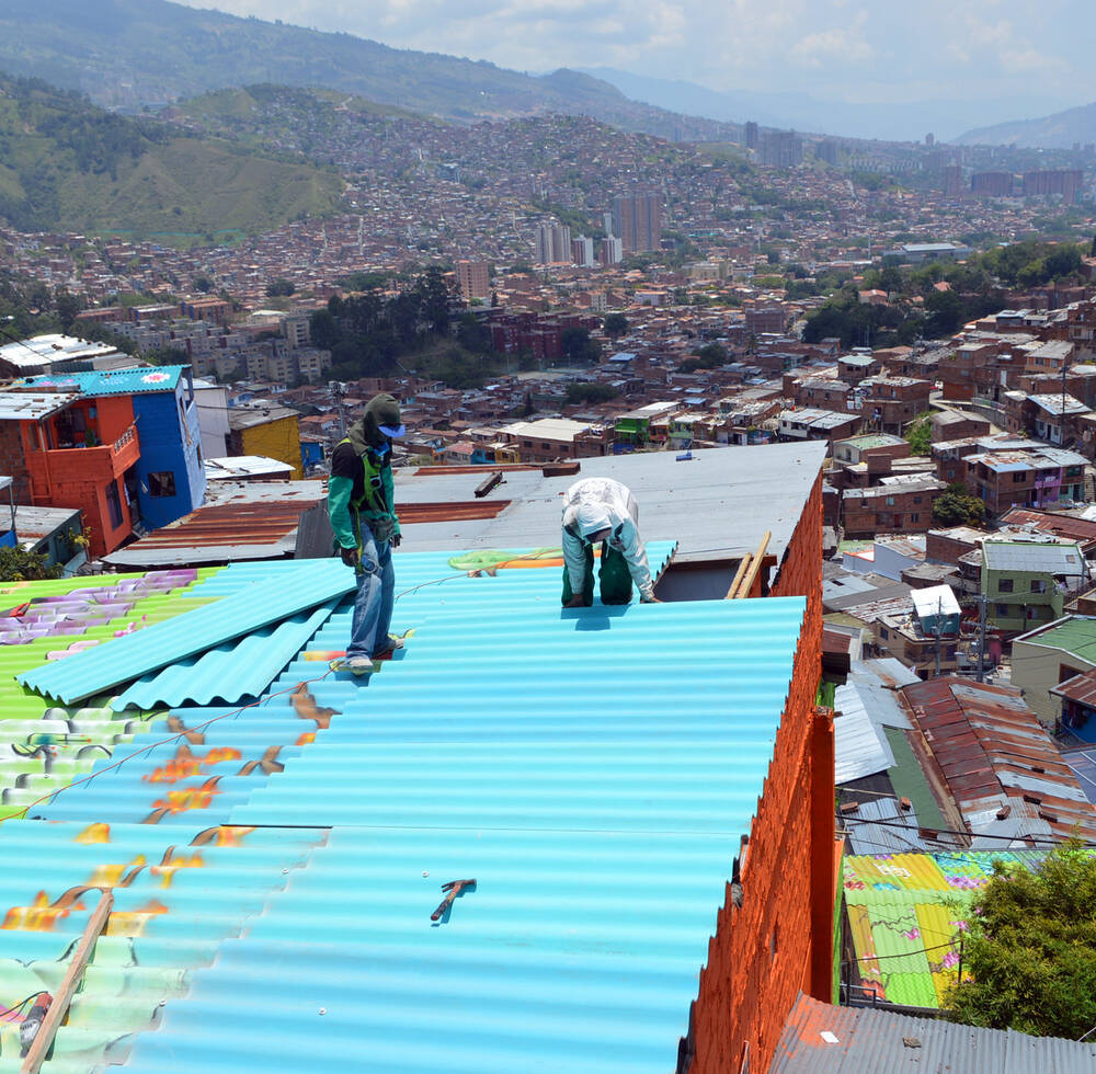 Local artist replace the old iron sheets with the new once in Medellin, Colombia