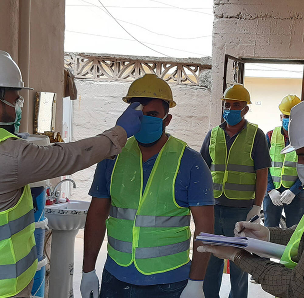 UN-Habitat workers undergoing through temperature check on entering construction site in Mosul