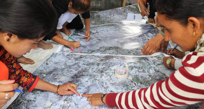 Four Nepalese residents point to a map while discussing sanitation issues.