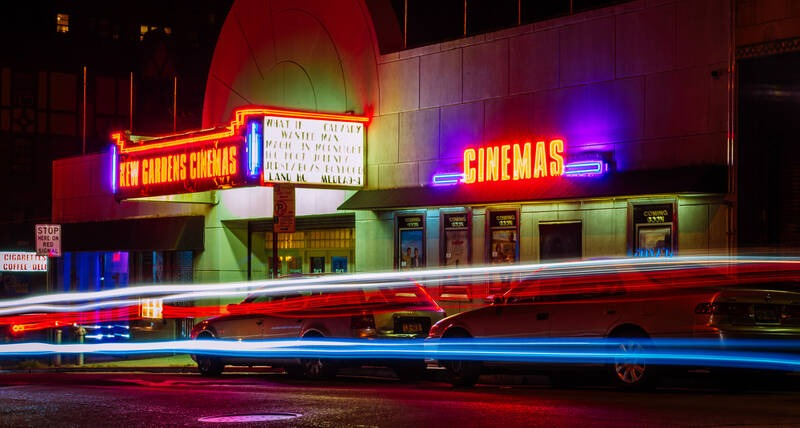 A exterior of a cinema at night