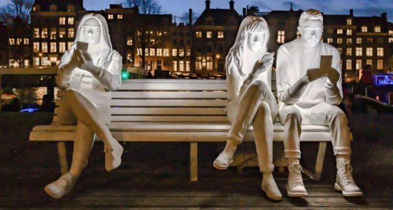 Sculpture of people looking at their phones