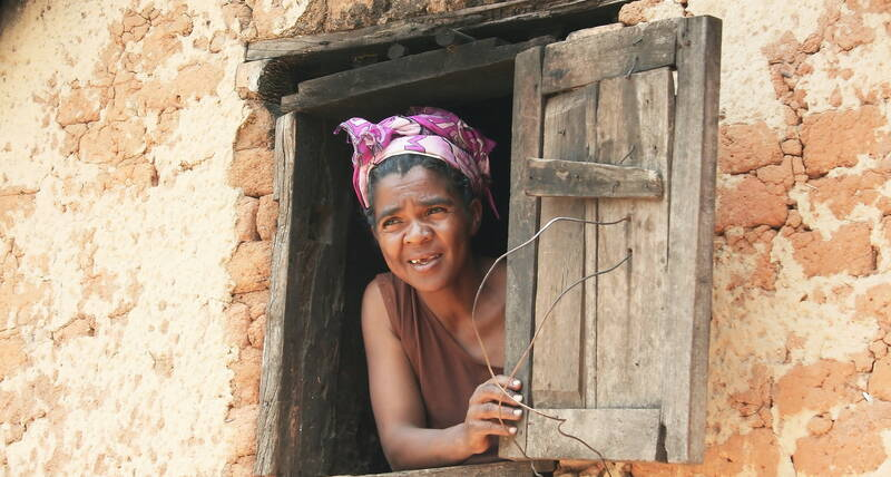 A woman peeps through a window in Madagascar. 2008.