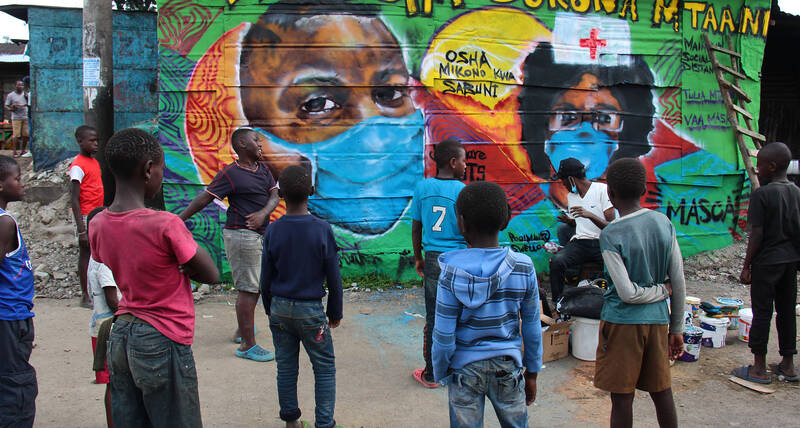 Children watch as a graffiti artist finishes one of the murals in the informal settlement of Mathare in Nairobi about COVID-19