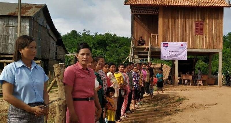 Families about to receive a new or rehabilitated house in Tboung Khmum, Cambodia welcome delegates to the official handover ceremony