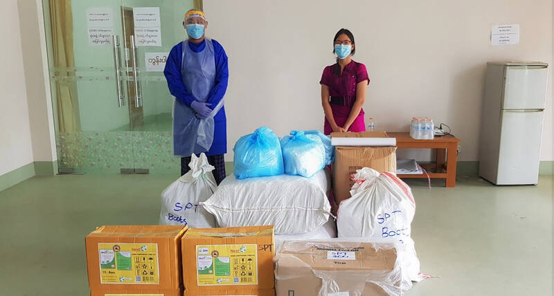A UN-Habitat staff member with the representative doctor at the Shwepyitha fever clinic to fight the Covid-19 pandemic