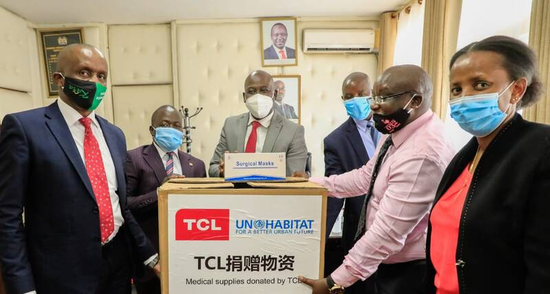 The Deputy Governor of Kenya's Nakuru Municipality, Erick Korir, receives a donation of masks from UN-Habitat, provided by the TLC Foundation, for youth managing the eight new permanent wash facilities and community health volunteers