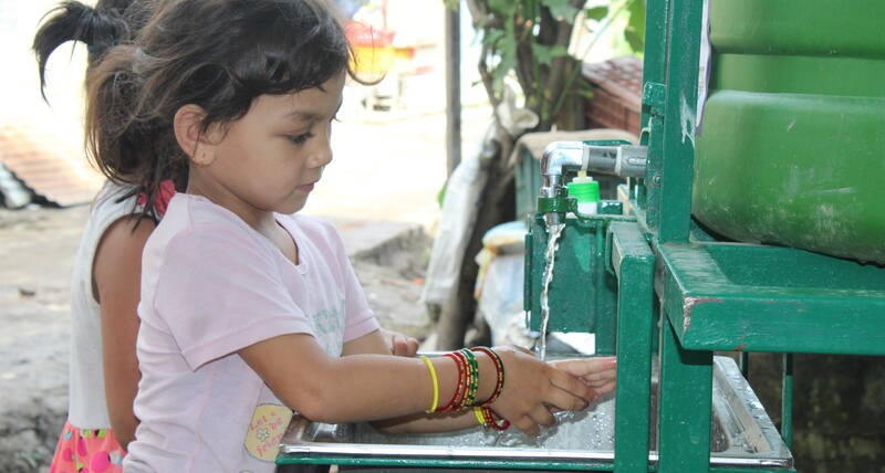 Children wash their hands to prevent the spread of COVID-19 in Bansighat, one of the informal settlements in Kathmandu, Nepal where UN-Habitat has installed touchless handwashing facilities