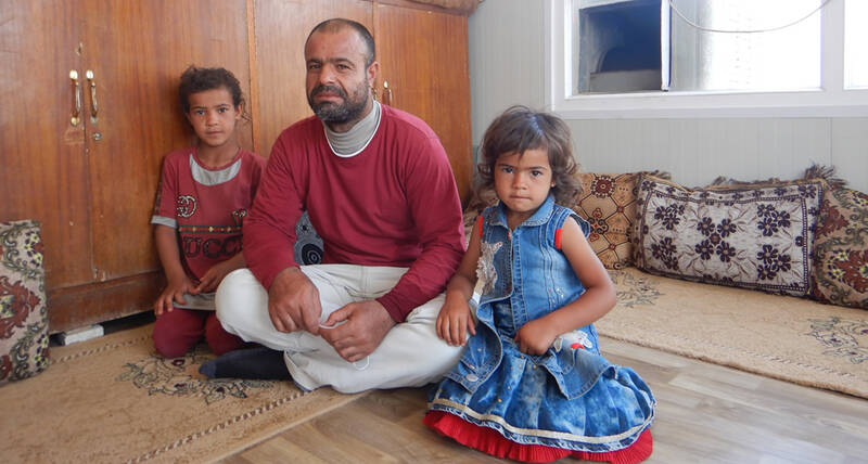Former park squatter Suliman Hassan Matar and two of his children in their new home in Mosul, Iraq provided under an EU funded rehabilitation project run by UN-Habitat