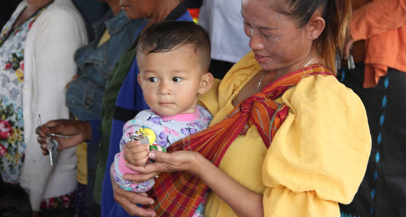 child holds a symbolic house key as the newly constructed houses were handed over to the people